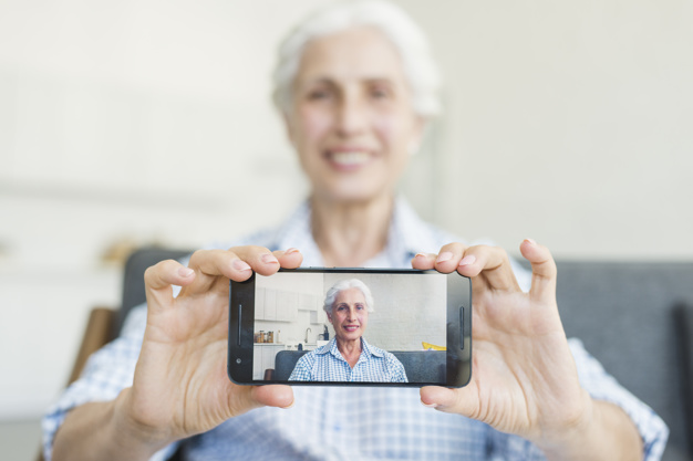 close-up-of-senior-woman-showing-her-photo-on-smartphone_23-2147918452