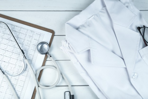 stethoscope-clipboard-and-doctor-s-uniform-on-white-neat-wooden-desk_1387-572